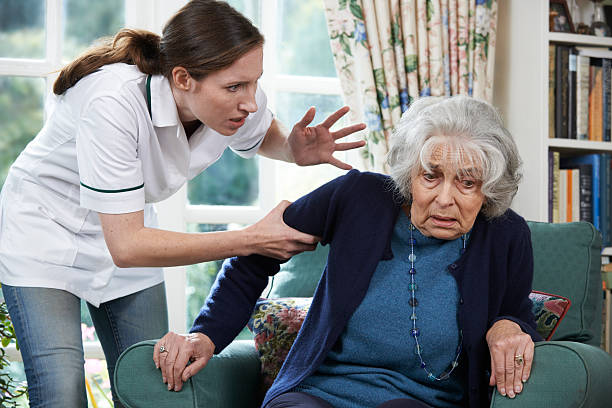 Care Worker Mistreating Senior Woman At Home Care Worker Mistreating Senior Woman At Home abuse stock pictures, royalty-free photos & images