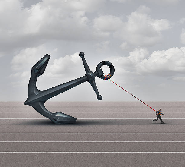 Career Burden Career burden and business stress concept as a businessman or worker pulling a giant heavy metal anchor as a metaphor for hardship and strugge with taxes or oppression. deadweight stock pictures, royalty-free photos & images