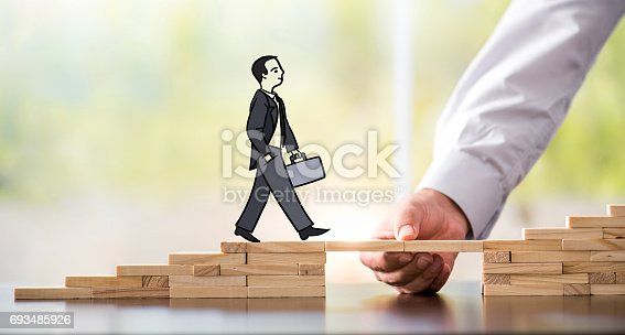 istock Career Planning Concept. Businessman Getting Help Building Bridges To Success. 693485926