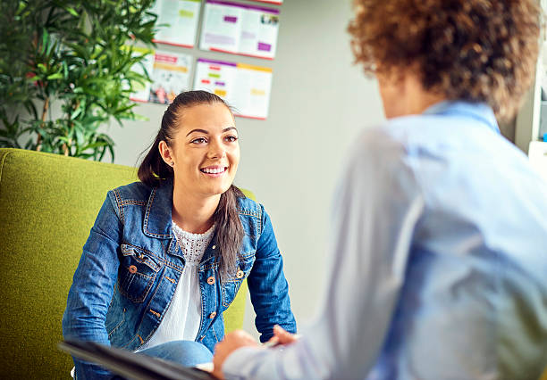 careers guidance counsellor a young woman sits opposite a counsellor and chats happily . They are sitting on armchairs in the counsellor's office . The young woman is smiling as she listens to the advice. counseling stock pictures, royalty-free photos & images