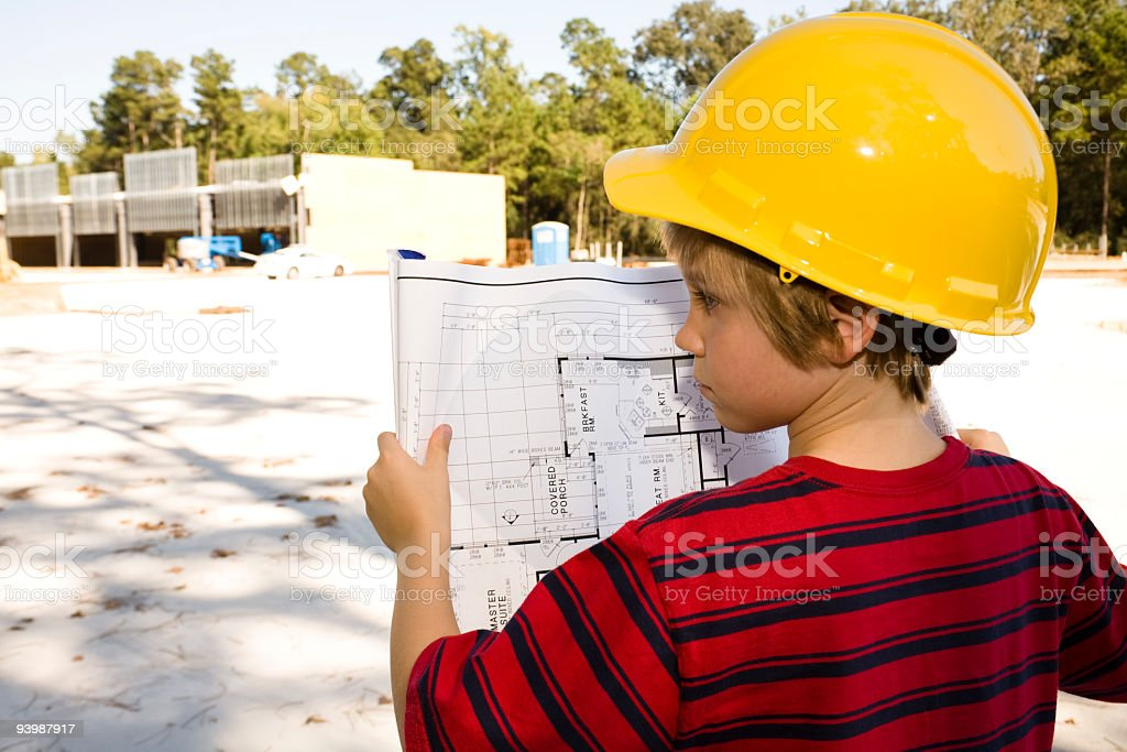 Careers: Young boy, job foreman. Blueprints, hardhat. Construction site. royalty-free stock photo