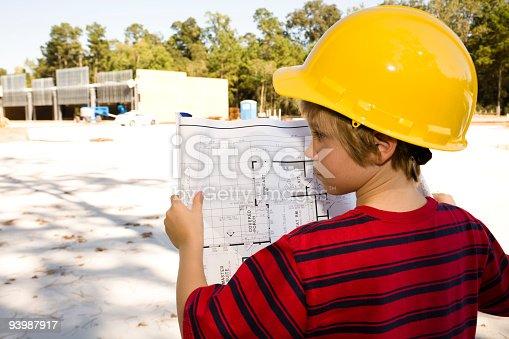 istock Careers: Young boy, job foreman. Blueprints, hardhat. Construction site. 93987917