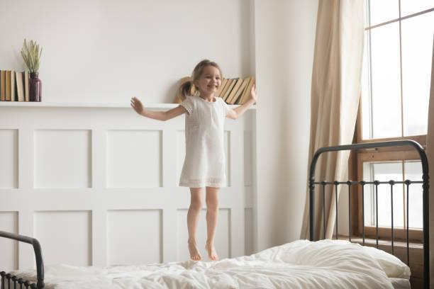 carefree aktif küçük kız yatakta atlama beyaz elbise giyiyor - beyaz elbise stok fotoğraflar ve resimler