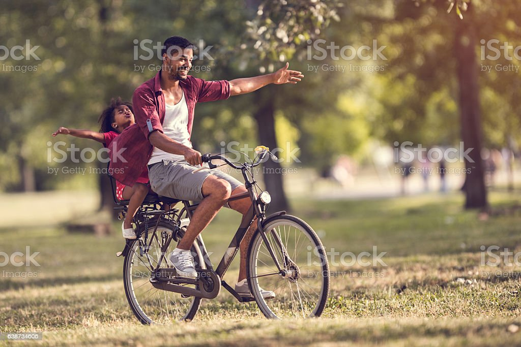 Carefree African American father and daughter cycling in the park. stock photo