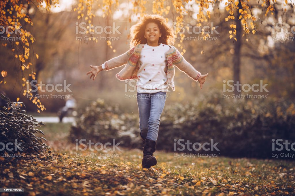 Carefree African American girl running with her arms outstretched in autumn day at the park. stock photo