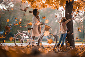 Happy African American mother with a bike enjoying with her daughter in autumn day.