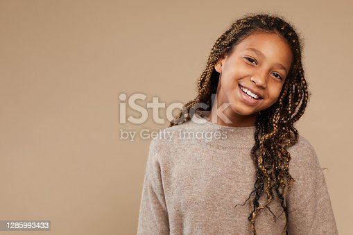Portrait of carefree African-American girl smiling happily at camera while standing against beige background in studio, copy space