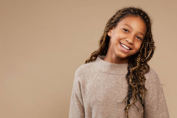 Carefree African-American Girl in Studio Portrait of carefree African-American girl smiling happily at camera while standing against beige background in studio, copy space girls stock pictures, royalty-free photos & images