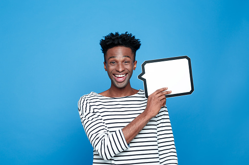 Carefree Afro American Guy Holding Speech Bubble Stock Photo - Download Image Now