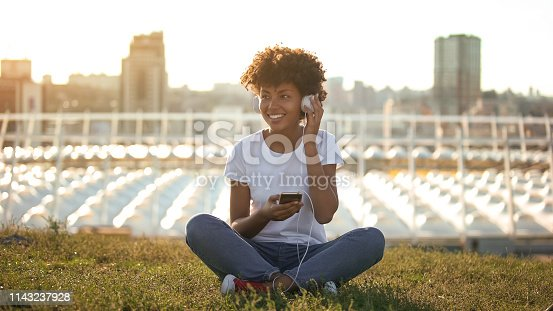 Carefree afro-american woman listening to music in headphones and enjoying youth