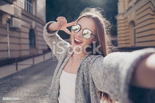 istock Carefree and happy, sunny spring mood. Cute young smiling girl is making selfie on a camera while walking outdoors. She is wearing casual outfit, mirror glasses 938502640