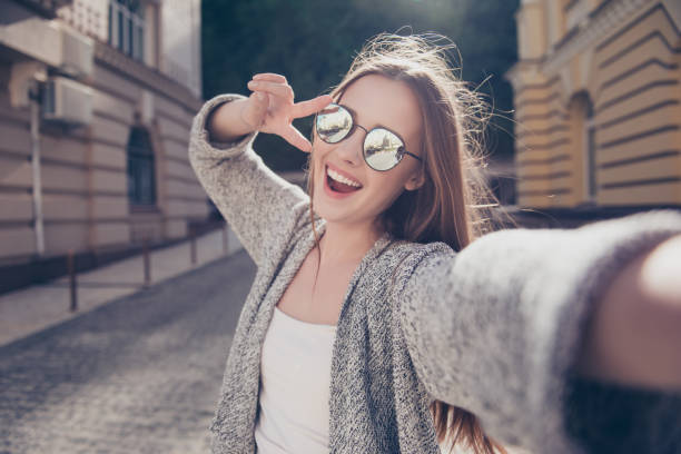 carefree and happy, sunny spring mood. cute young smiling girl is making selfie on a camera while walking outdoors. she is wearing casual outfit, mirror glasses - selfie foto e immagini stock