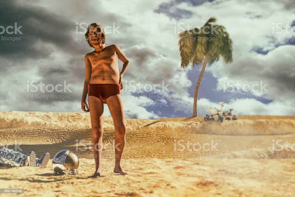 Carefree astronaut stranded on beach far away from Earth stock photo
