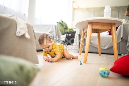 istock Carefree baby boy crawling on floor 1178993151