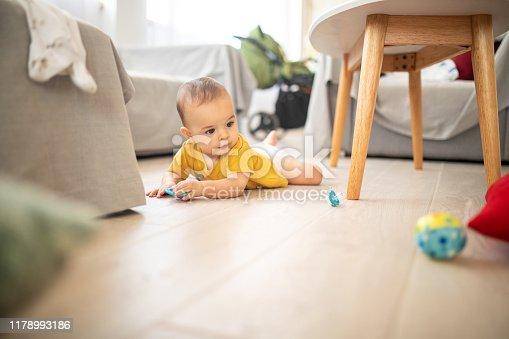 istock Carefree baby boy crawling on floor 1178993186