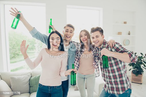 istock Carefree, beautiful, funky, fancy, joyful, glad youngster people waving hello and happily look into the camera holding in their hands green glass bottles with a drink 1056221176