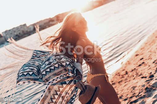 Attractive young woman smiling while standing on the beach outdoors