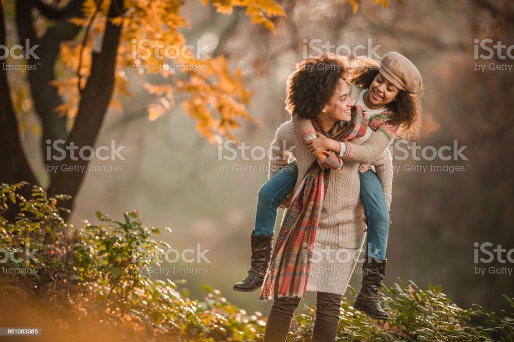 Carefree black mother piggybacking her daughter in autumn day at the park. stock photo
