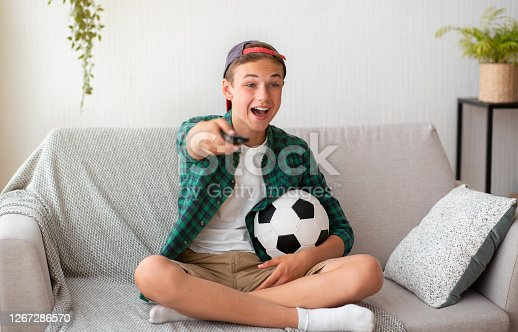 Carefree boy watching football chanels on TV at home, spending time alone, having fun, copy space
