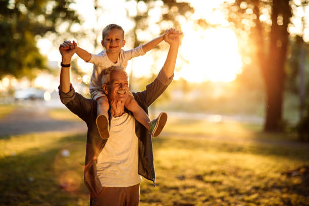 Carefree child and a happy grandpa Happy grandpa carrying his cheerful grandson on the shoulders in the sunny park grandson stock pictures, royalty-free photos & images