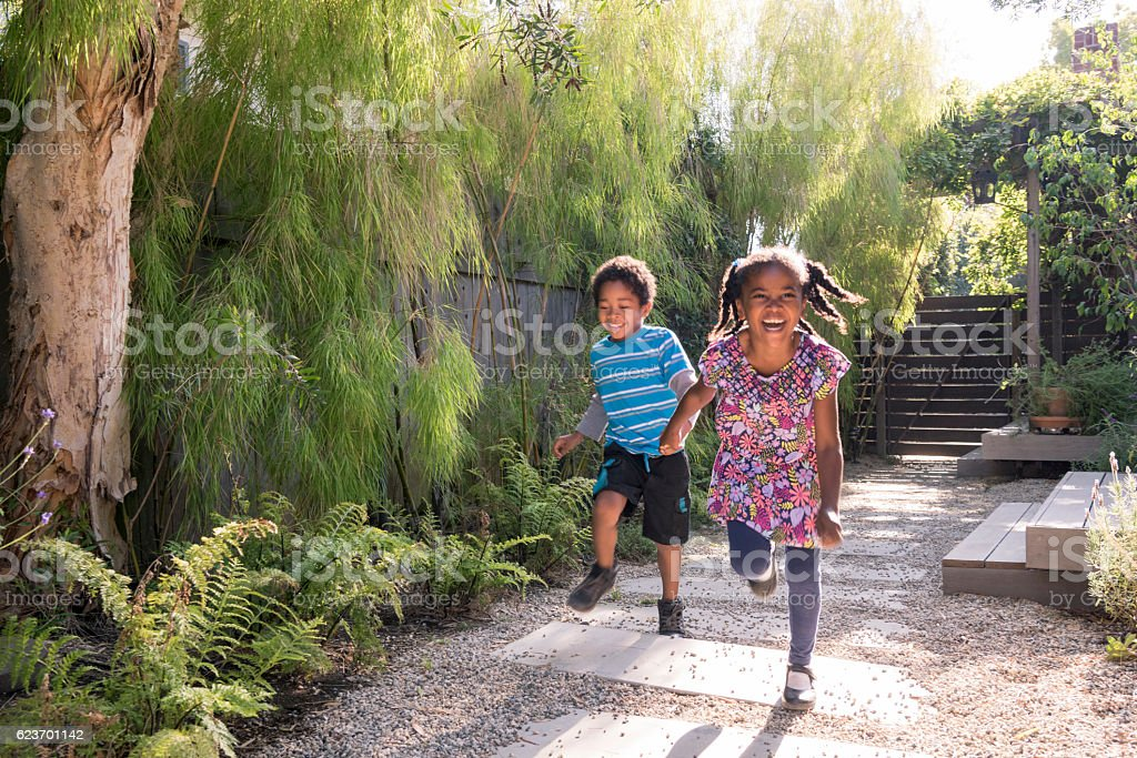 Carefree children running and playing in garden stock photo