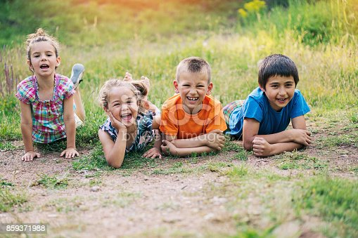Group of small children lying down on a dirt road