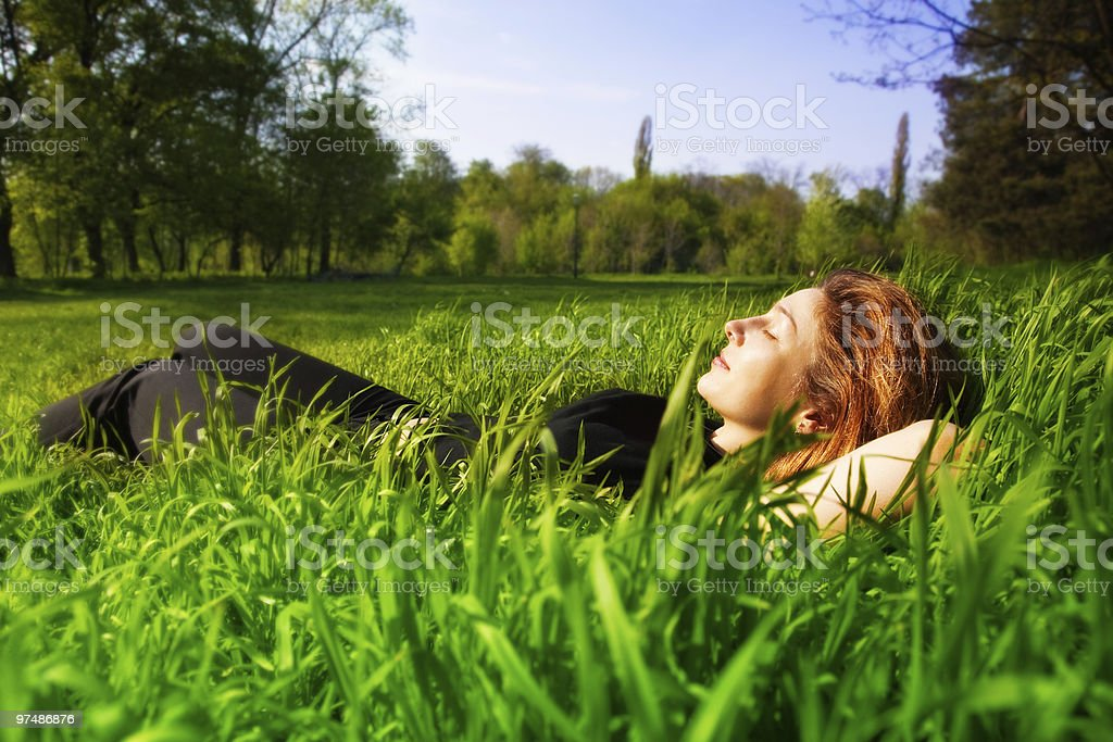 Carefree concept - woman relaxing outdoor in grass royalty-free stock photo