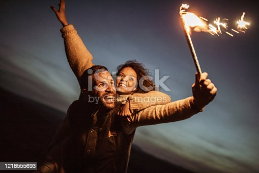 Young happy couple piggybacking and having fun with flaming torch by night. Focus is on man.