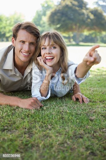 Carefree couple lying in the park with woman pointing on a sunny day
