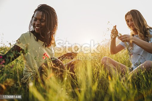 Two young cheerful multi-ethnic female friends enjoying time together in nature, weave wreaths of flowers