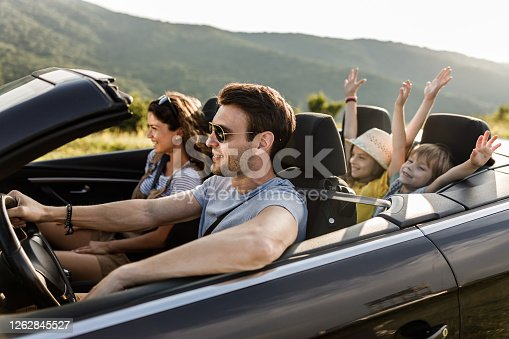 Happy parents and their small kids going on road trip in convertible car. Focus is on man.