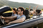 istock Carefree family having fun during road trip by convertible car. 1262845527