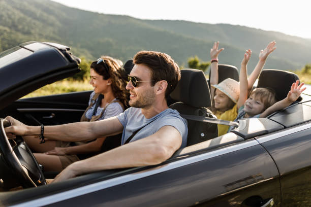Carefree family having fun during road trip by convertible car. stock photo