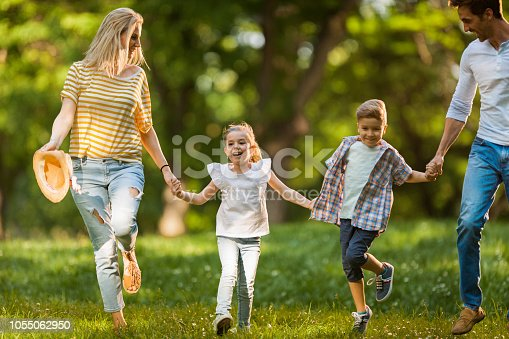 istock Carefree family having fun while running in the park. 1055062950