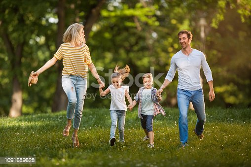 istock Carefree family having fun while running in the park. 1091689628