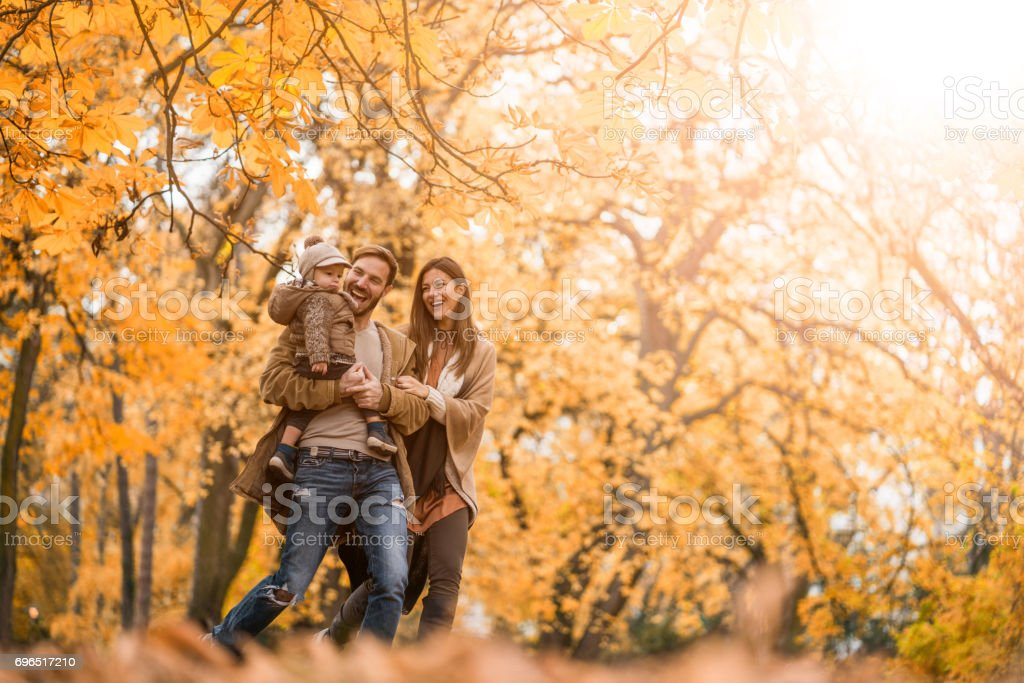 Carefree family having fun while running in the park. stock photo