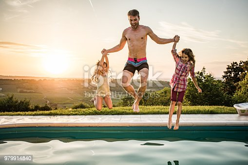 Happy father and daughters holding hands and having fun while jumping together in the swimming pool at sunset.
