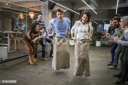 istock Carefree freelancers having fun during a sack race at casual office. 918430556