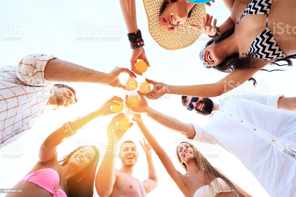 Carefree friends cheering with beer on beach stock photo