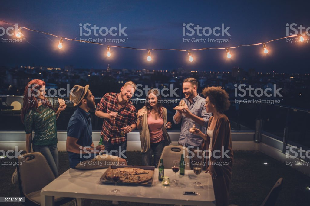 Carefree friends having fun on a night party at penthouse terrace. stock photo