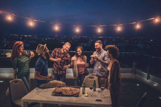 unbeschwerte freunde, die spaß an einem abend party im penthouse-terrasse. - terrassen lichterketten stock-fotos und bilder