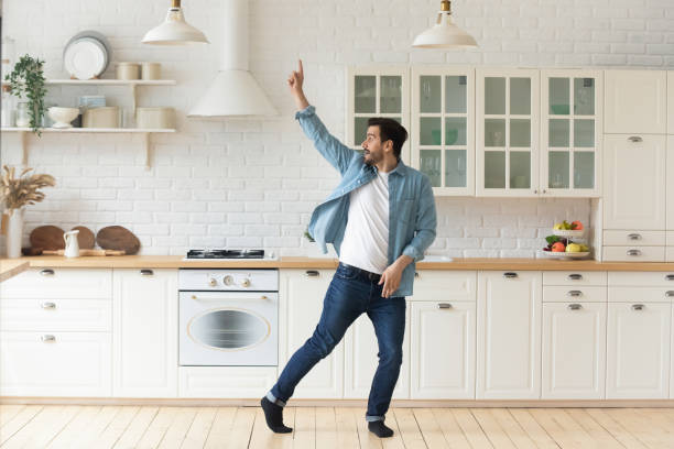 Carefree funny young man having fun dancing alone in kitchen Carefree funny young man having fun dancing alone in modern kitchen interior, active happy funky single guy enjoying silly movements dance standing at home listening music celebrating freedom concept fresh start morning stock pictures, royalty-free photos & images