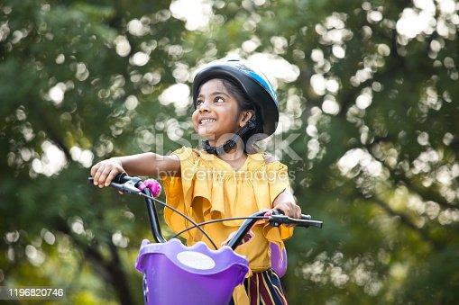 Carefree girl riding bicycle at park