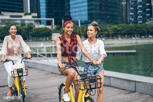 Carefree girlfriends enjoying biking and having fun in the city