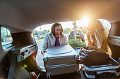 Two women tourists loading a heavy bag into the back of an estate car with the boot open. Photo of Happy female couple on a vacation, taking their luggage out of car boot. Beautiful multiracial friends on a road trip.