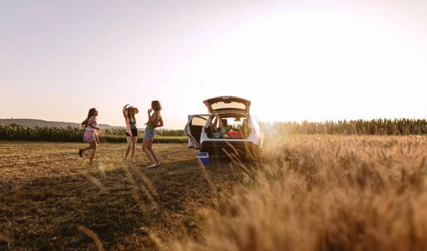 Unbekümmerte Mädchen tanzen hinter ihrem Auto, während sie sich von reisen – Foto