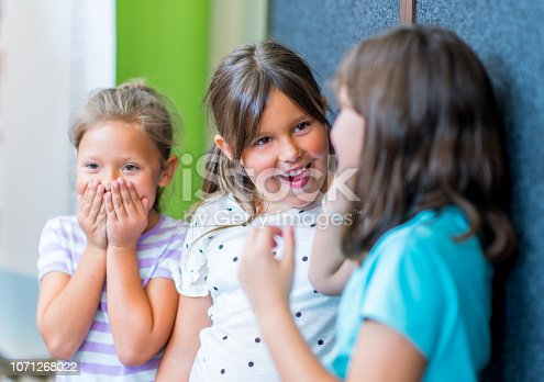 Shocked girls looking at friend in school. Happy friends are sharing secrets while standing together. They are wearing casuals.