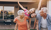 Carefree grandparents piggybacking their joyful grandkids in the front yard.