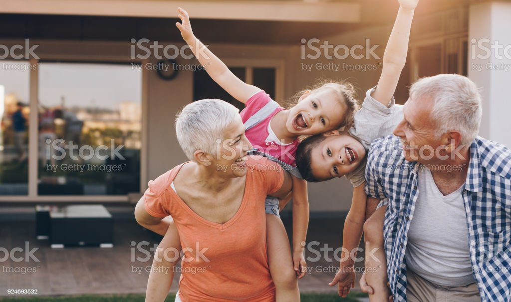 Carefree grandparents piggybacking their joyful grandkids in the front yard. stock photo