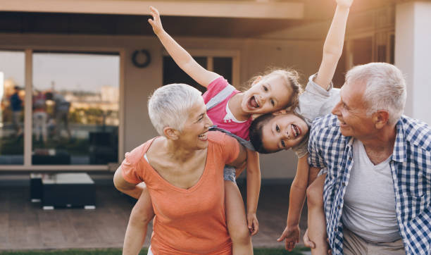 carefree grandparents piggybacking their joyful grandkids in the front yard. - grandparents stock photos and pictures